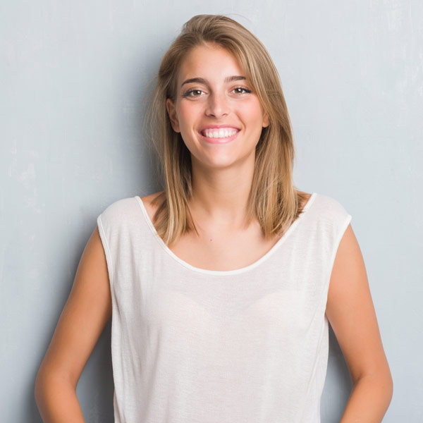 woman leaning against wall smiling